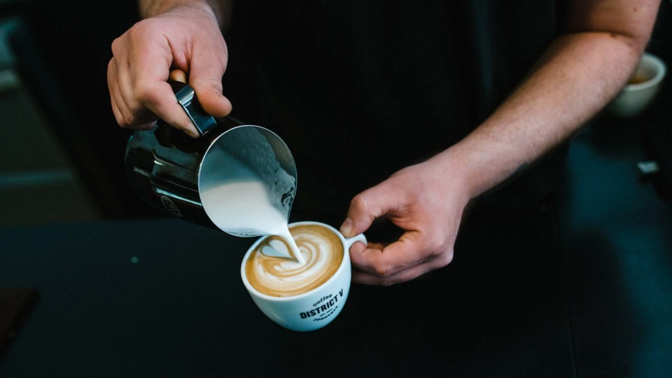 tide stories district five coffee roaster mann gießt milchschaum in kaffeetasse